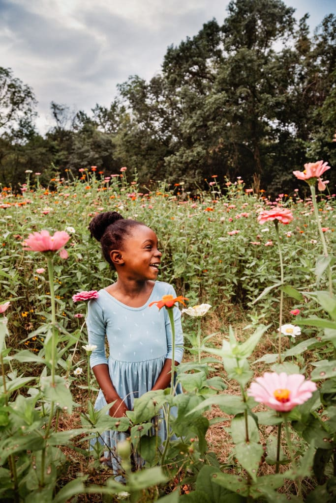 Family Photographer, happy beautiful little girl smiles in a field of pink flowers