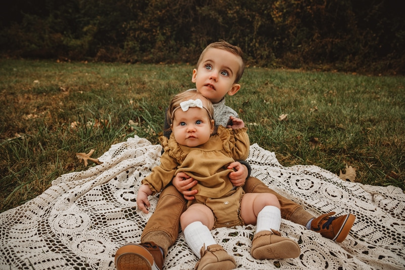 Newborn Photography, Older brother holds baby sister close while they sit on a blanket in a grassy area