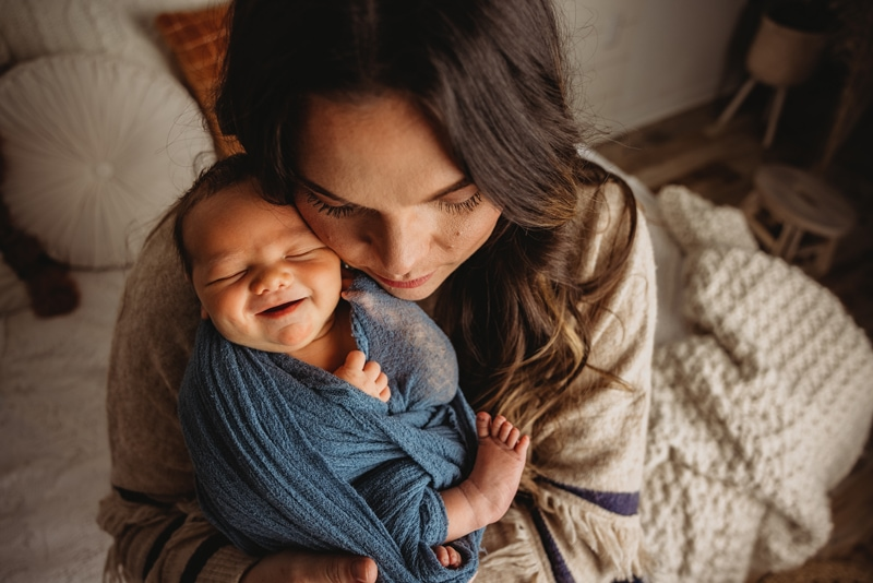 Newborn photography, mother holds happy baby close back at home snuggled on couch
