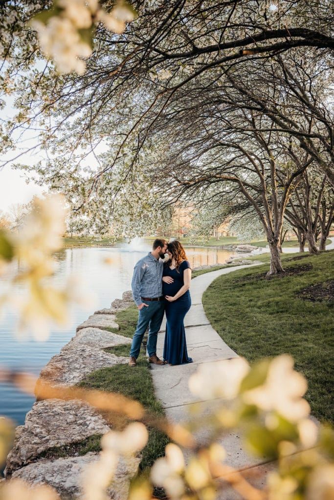 Family Photographer, Man and woman draw near on lakeside path beneath trees